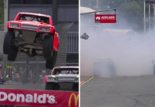 truck going over a mcdonald's ramp, the race track is covered with smoke