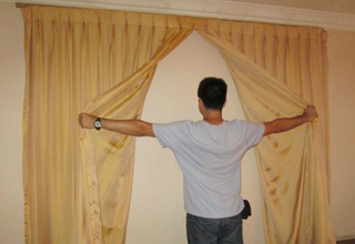 Man opens hotel curtains to unveil a windowless wall