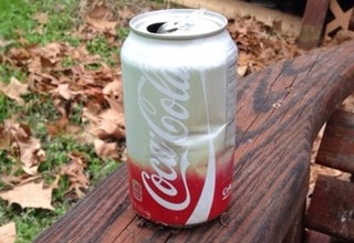 Can of coke color-split from aging outdoors in cupholder