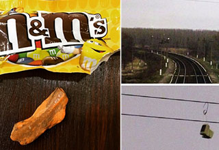 m&m with a weird orange freakish one next to the bag. Monitor hanging from a power line near a train