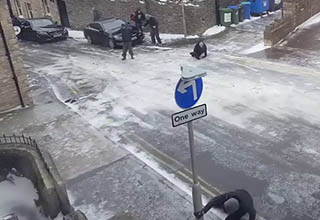 guy desperately reaching for a sign post while others fall on an icy British road