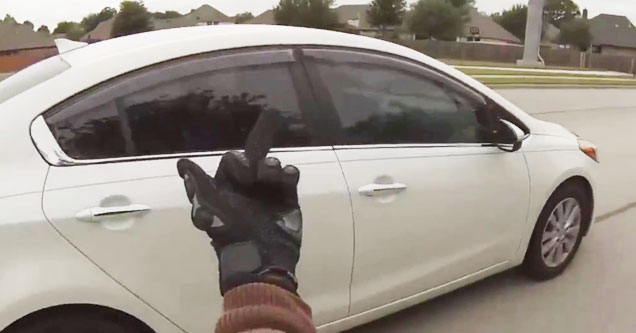 a biker flips the bird to a man driving a white car with tinted windows