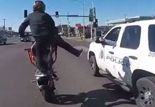 a man on a motorcycle kicking at a police SUV