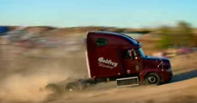semi truck driving up a dirt jump