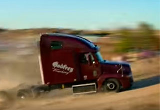 semi truck driving up a dirt jump