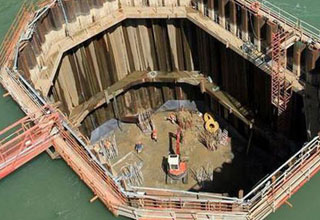 a photo of a bridge pillar being built in drained area of a lake