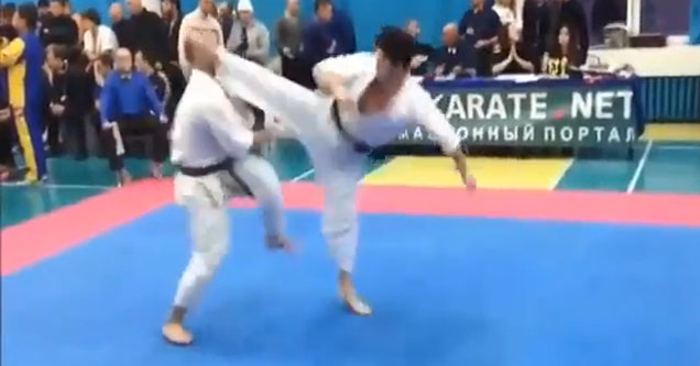 two men in karate gis fighting in the ring one is getting kicked in the head