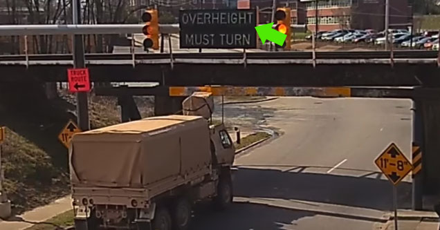 a covered military truck going under a short bridge with a green arrow pointing to a sign telling the truck to turn