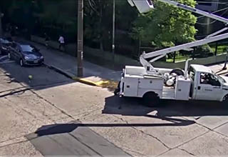 crane running into powerlines as a man in a hardhat looks on helplessly.