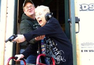 an old woman with a walker shooting a gun