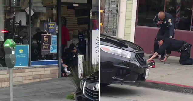 cops crawls along the ground as another cop helps him on a san fransisco street