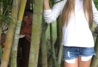 a girl standing by bamboo and people hiding behind her