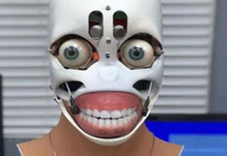 a freaky looking robot face  with human eyes and teeth