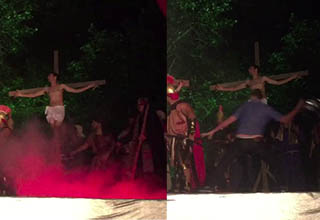 people reenacting the crucifixing with red smoke coming up, man holding a helmet swings at an actor