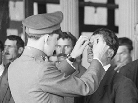 man checking another mans eyes