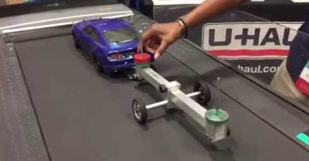 a blue toy car on a treadmill towing a trailer