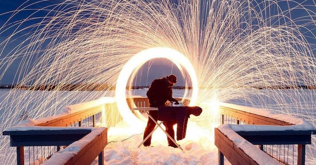 a man using a grinder making a perfect circle of sparks