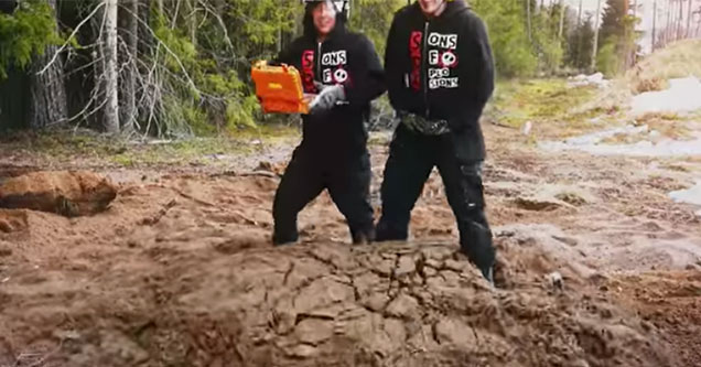 two guys standing on a pile of dirt
