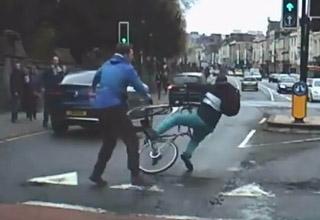 man in blue shirt knocks a cyclist off his bike