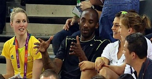 kobe holding his hands out to demonstrate something with tons of people watching him