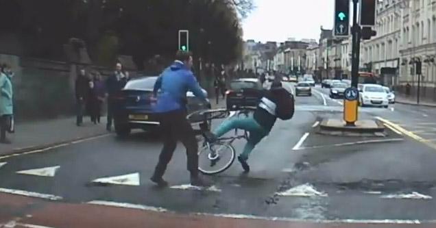 man in blue shirt knocks a cyclist off his bike