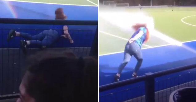 lady falls on a blue tarp, the same lady gets sprayed with a sprinkler on a football field