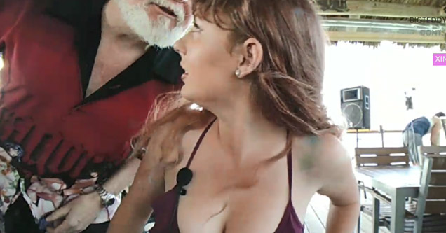 an old man wearing a red shirt with a white beard leans in to talk to this busy girl in bikini