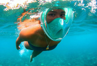 Woman snorkeling with a full face snorkel mask