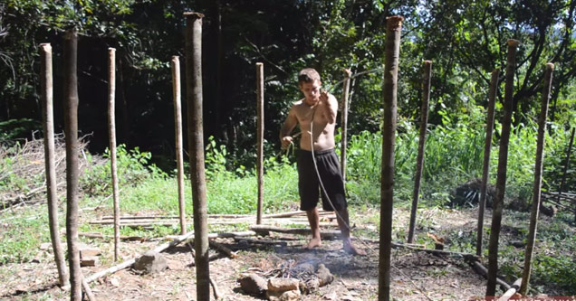 a shirtless man wearing shorts burring posts into the dirt in the woods g0kv7q5y1