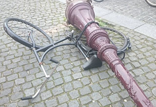 a bicycle lying beneath the light pole it was tied to after the light pole fell down