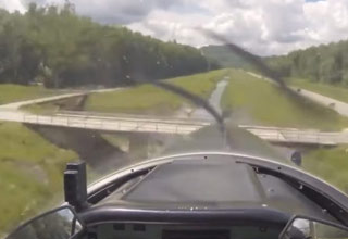 first person view from inside an airplane flying over a bridge