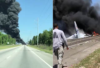 smoke pours from a plane that crashed on a savannah highway, a man with a gun in his holster walks towards the plane