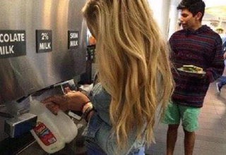 girl fills her milk container from the cafeteria coffee station