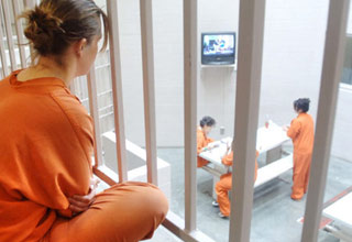 a female inmate in an orange jump suit sitting behind bars