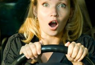 a woman driving a car with a surprised look on her face