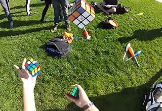 man juggling rubiks cubes in a park green