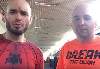 two white bald mma fighters in a gym