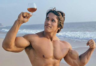 Arnold Schwarzenegger on a beach flexing while looking at a glass of cognac