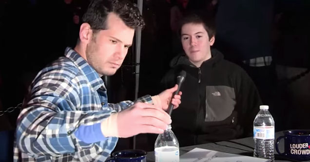 two white guys sitting at a table in the dark talking