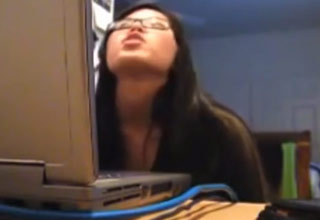 an asian girl makes a funny face while on the computer in her room