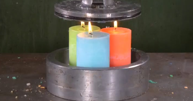 a red green and blue candle inside a hydraulic press