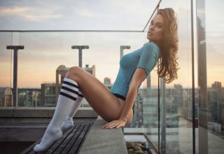 a hot girl in knee high socks and blue shirt sitting on edge of building