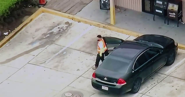 a man in an orange vest getting out of a black parked car