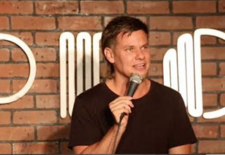 theo von standing in front of a brick wall