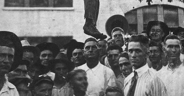 a group of white people posing with a hanging man