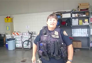 a police officer looking at the camera and talking from the police garage, she is wearing a vest