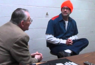 a man in a brown jacket interviews an inmate in a blue jumpsuit and orange hat