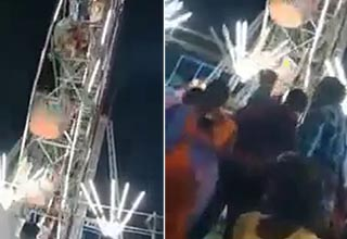 ferris wheel slanted in the frame, people huddled as it begins to topple