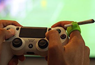 a man holding a playstation controller wearing a green ring that is a cigarette holder
