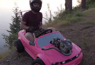 a man wearing a motorcycle helmet drives a pink babrie 4wheeler with a dirtbike motor